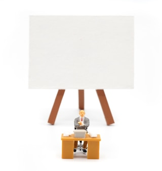 Miniature enseignant devant un tableau noir sur fond blanc. retour au concept de l'école.