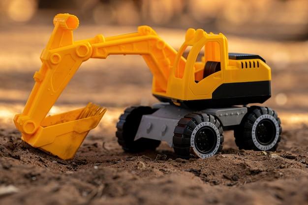 Miniature d'excavatrice de jouet de couleur jaune et noire au sol avec mise au point sélective