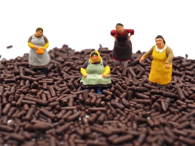 Miniature de grosses femmes sur des pépites de chocolat sur fond blanc. concept de régime, de graisse et de perte de poids.