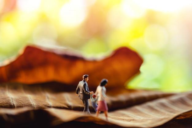 Miniature de père, mère et fils, tenant les mains et marchant sur une feuille sèche dans le parc