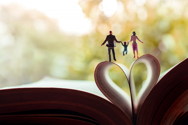 Miniature de père, mère et fils tenant les mains et marchant vers le livre sur un rouleau de pages en forme de cœur