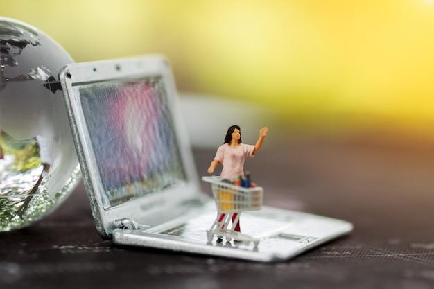 Miniature de personnes avec un panier d'achat sur un ordinateur portable et un globe terrestre