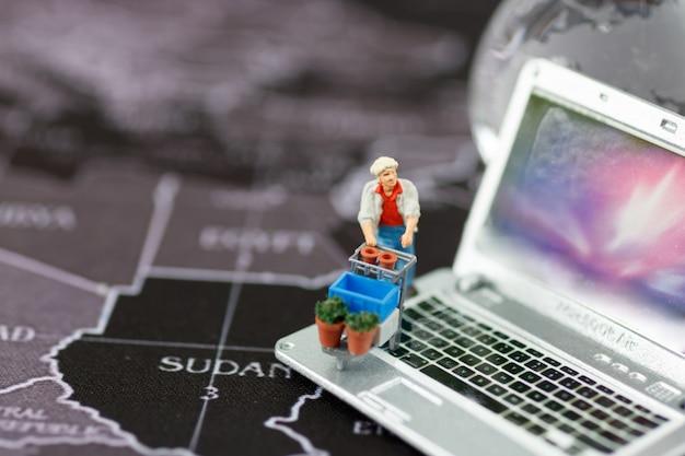 Miniature de personnes avec un panier sur un ordinateur portable