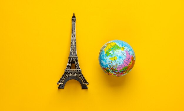 Minimalisme voyage encore la vie. figurine de la tour eiffel, globe sur fond jaune