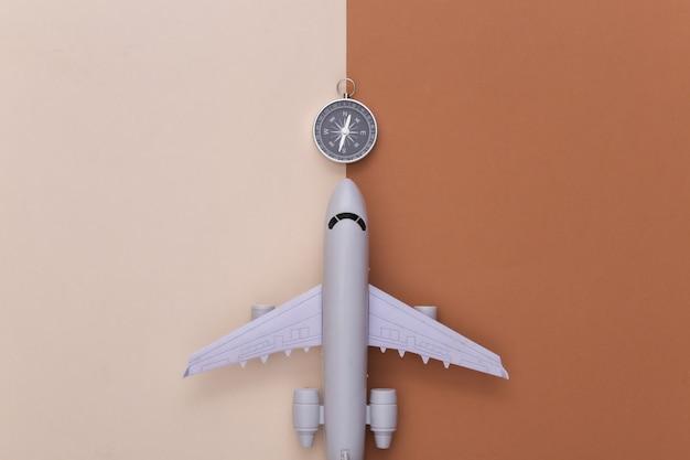 Le minimalisme voyage à plat. boussole et avion sur fond marron beige. vue de dessus