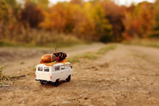 Minivan miniature de voiture de jouet porte sur le toit des feuilles jaunes
