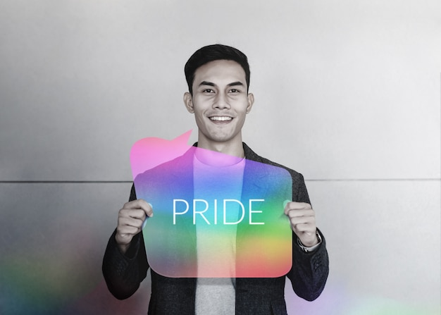 Minorités sexuelles et concept lgbt. heureux jeune gay souriant et montrez le texte de fierté sur la carte arc-en-ciel