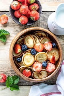 De minuscules crêpes aux céréales et au chocolat dans un bol en bois avec du miel et des fraises