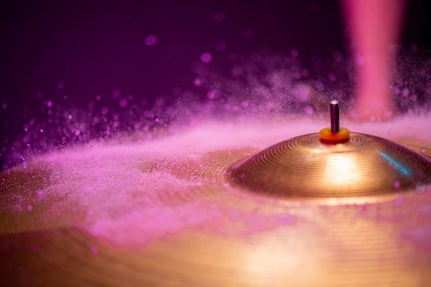 De minuscules gouttes d'eau frappant cymbale de couleur dorée sur fond violet avec fond en haut à gauche pour votre annonce ou message