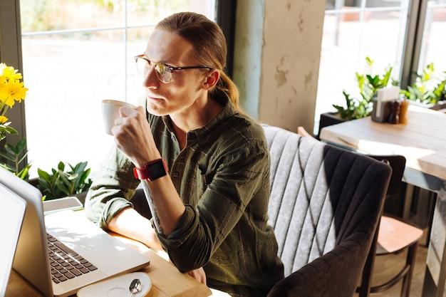 Minute pour se détendre. bel homme sérieux ayant un regard pensif tout en faisant une pause café