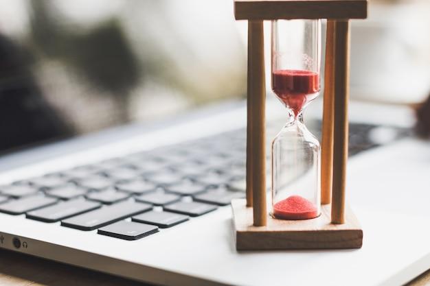 Minuterie d'horloge de sable sur ordinateur portable .symbol de temps