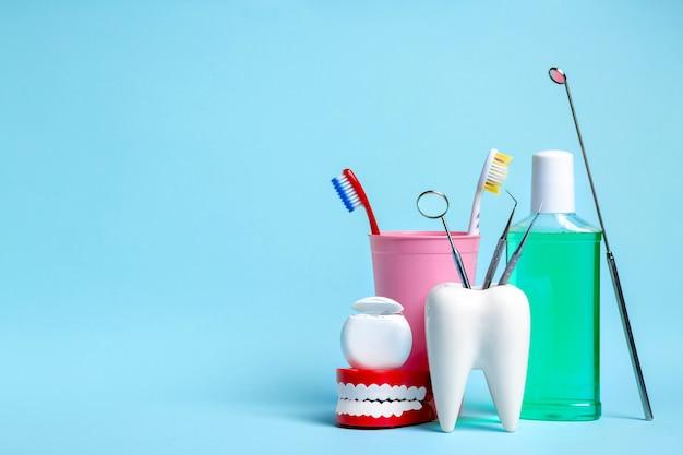 Miroir dentaire avec sondes d'exploration en modèle de dents blanches saines près de la soie dentaire, de la mâchoire humaine, du rince-bouche et des brosses à dents en verre rose sur fond bleu clair