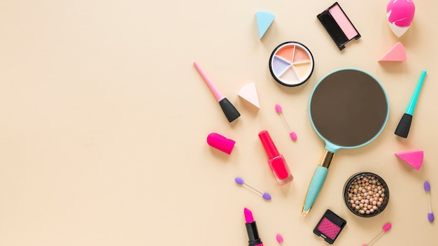 Miroir avec différents produits de beauté sur une table beige