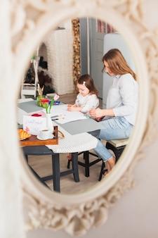 Miroir de mère et fille en train de peindre