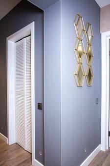 Miroir à la mode au coin du mur gris de l'appartement.