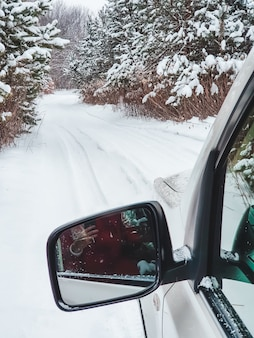 Miroir de voiture devant avec vue sur le sentier enneigé dans l'espace de copie de la forêt