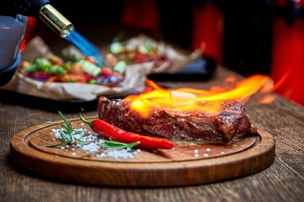 Mise au point douce. entrecôte boeuf viande de steak grillée avec flammes de feu sur planche à découper en bois avec branche de romarin, poivre et sel. master chef cuisinant un délicieux barbecue grill. faire fondre le beurre