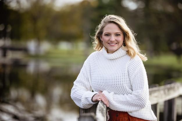 Mise au point peu profonde d'une femme appuyée contre une clôture en bois et souriant à la caméra