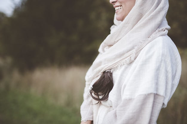 Mise au point peu profonde d'une femme portant une robe biblique et souriant dans un champ