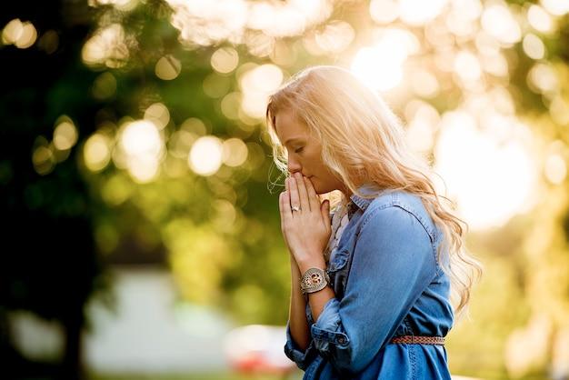 Une mise au point peu profonde d'une femme en prière