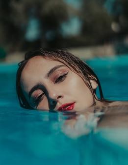 Mise au point peu profonde d'une jeune femme portant du rouge à lèvres rouge dans une piscine par une journée ensoleillée