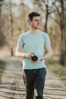Mise au point peu profonde d'un photographe masculin adulte tenant un appareil photo et marchant dans un parc