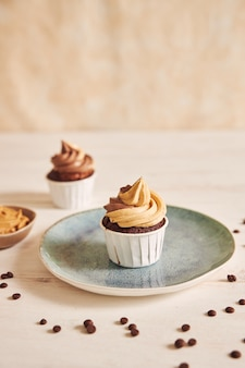 Mise au point peu profonde verticale gros plan de délicieux cupcake au beurre d'arachide avec glaçage crémeux sur plaque