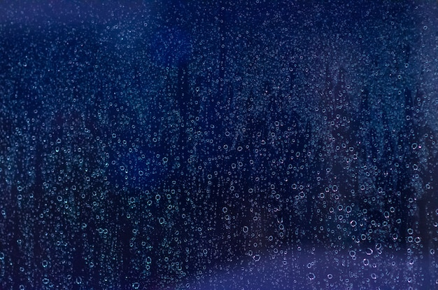 Mise au point et photo floue de rain drop sur la vitre en bleu foncé