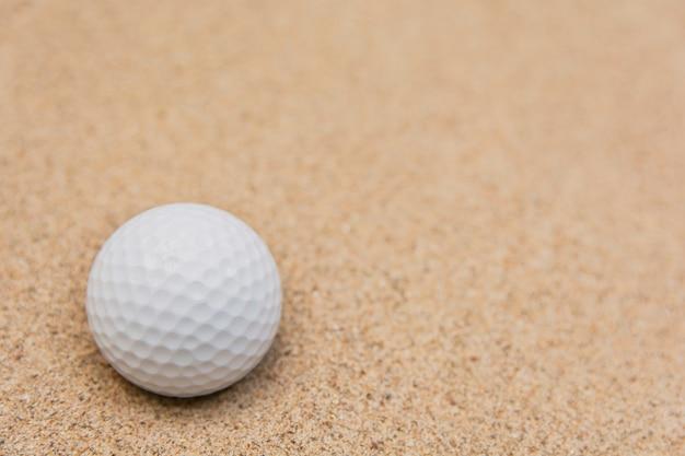 Mise au point sélective d'une balle de golf blanche sur un bunker en sable