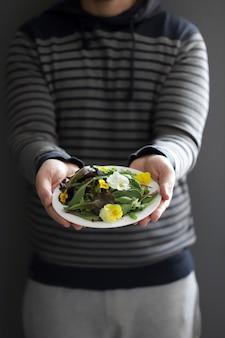 Mise au point sélective. un beau mélange de salades avec des fleurs sur une assiette blanche est tenu par un homme. concept de régime. nourriture végétalienne saine.