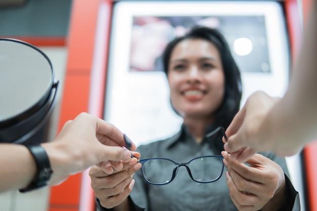 Mise au point sélective d'une belle vendeuse donnant une paire de lunettes aux mains du client lors de son essai dans un magasin de lunettes