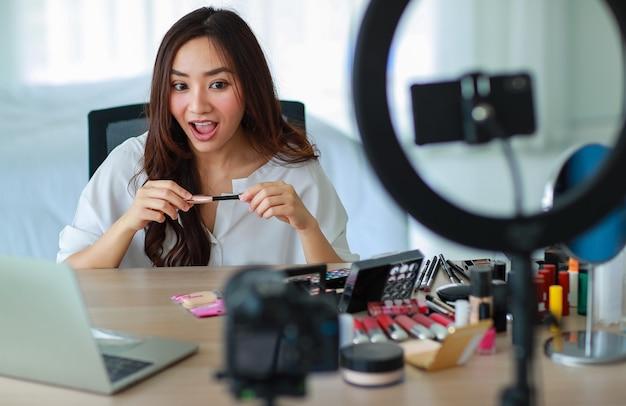 Mise au point sélective sur la caméra, jeune et belle fille asiatique montre comment utiliser le rouge à lèvres pour la caméra avec le sourire et heureuse lors de l'enregistrement vidéo diffusé sur le contenu et l'examen des cosmétiques.