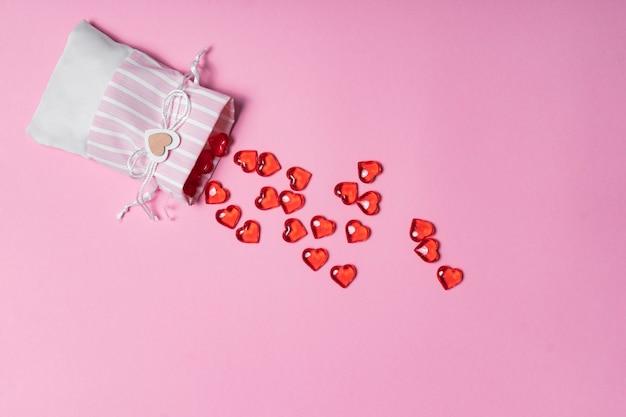 Mise au point sélective. carte de la saint-valentin. coeurs rouges en verre dispersés dans un beau sac en tissu. la vue du haut. fond rose