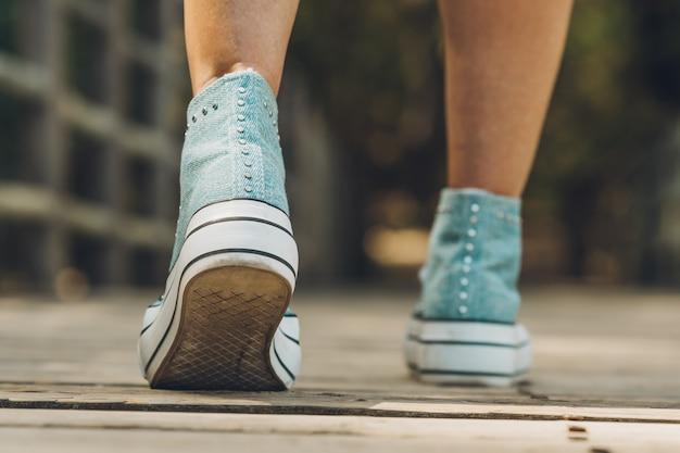 Mise au point sélective sur les chaussures en jean ornées d'une femme marchant le long d'un pont rural