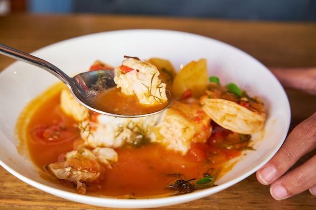 Mise au point sélective sur une cuillère avec du poisson d'une casserole avec des pommes de terre à la morue et aux crevettes et de l'aïoli au poivre de palme dans une table en bois
