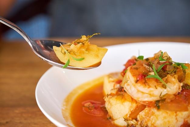 Mise au point sélective sur une cuillère avec un morceau de pomme de terre d'une casserole avec de la morue et des crevettes avec des pommes de terre et de l'aïoli au poivre de palme dans une table en bois