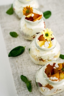 Mise au point sélective de délicieuses et douces glaces à la vanille dans des bocaux en verre décorés de fleurs jaunes