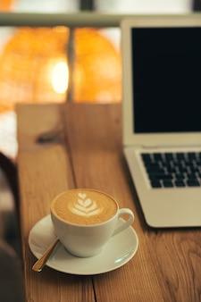 Mise au point sélective d'un délicieux café avec du latte art placé sur l'assiette sur une table en bois. ordinateur portable en arrière-plan