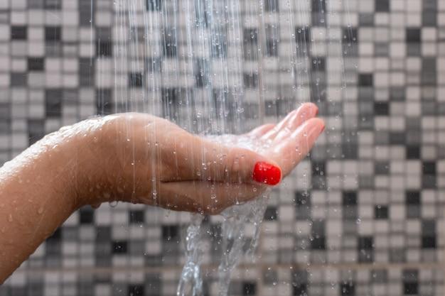 Mise au point sélective douce des mains et des gouttelettes d'eau de la douche