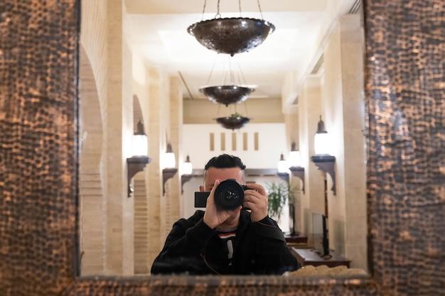 Mise au point sélective douce de l'objectif avec photographe masculin floue prenant une photo de lui-même dans le miroir