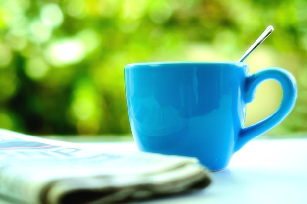 Mise au point sélective et douce de la tasse de café bleu avec journal flou et fond vert naturel