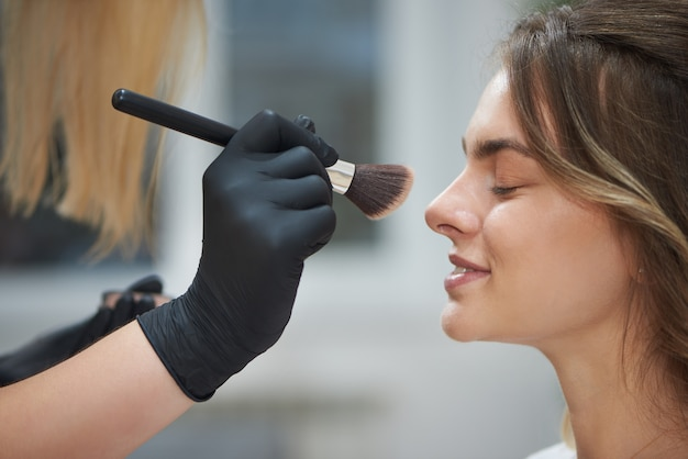 Mise au point sélective du client obtenant un maquillage professionnel dans un salon de beauté