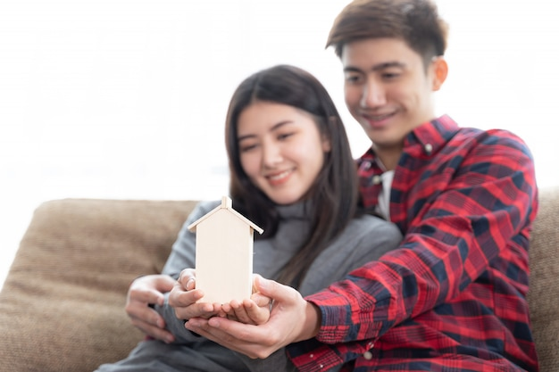 Mise au point sélective du jeune couple tenant la mini maison en bois sur le canapé de la chambre