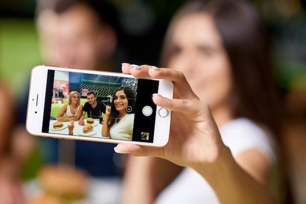 Mise au point sélective du téléphone prenant selfie d'amis