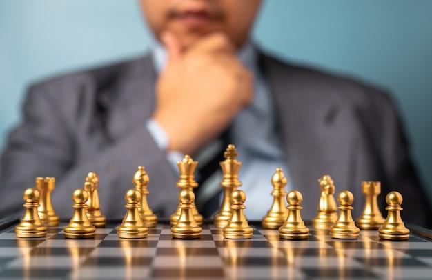 Mise au point sélective des échecs dorés devant l'homme d'analyse professionnelle.