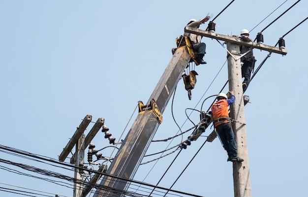 Mise au point sélective d'électriciens fixant une ligne de transport d'électricité sur un poteau électrique