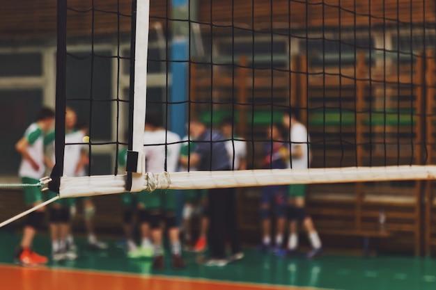 Mise au point sélective : l'entraîneur analyse le jeu de l'équipe de volley-ball pendant le temps mort dans la salle de sport. contexte pour le jeu de volley-ball en équipe. concept de sport, de mode de vie sain et de réussite en équipe. espace de copie