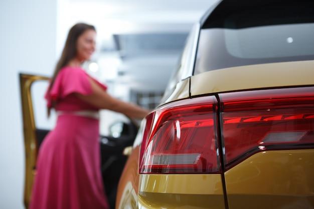 Mise au point sélective sur les feux de voiture, cliente regardant à l'intérieur d'une voiture chez le concessionnaire