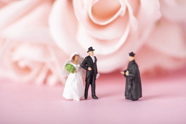 Mise au point sélective de figurines miniatures de la mariée, du marié et du prêtre