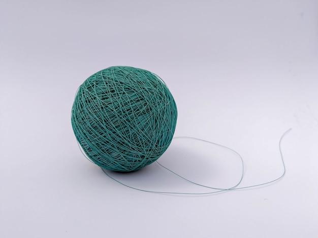 Mise au point sélective d'un fil de fil turquoise isolé sur fond blanc